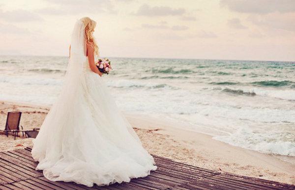 Bride-on-beach-daydreaming-35219736-600-388